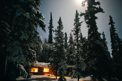 Cabina de registro acogedora en la noche iluminada por la luna del invierno Foto de archivo