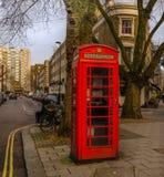 Cabina de teléfono roja en la esquina de la calle Fotos de archivo