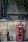 Cabina de teléfono y bicyle rojos Foto de archivo libre de regalías