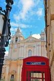 Cabina de teléfono y catedral de Mdina foto de archivo