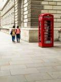 Cabina de teléfonos roja clásica de Londres con dos personas Fotos de archivo