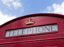 Cabina de teléfonos roja con el cielo azul Foto de archivo libre de regalías
