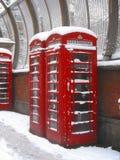 Cabina de teléfonos roja en la nieve Foto de archivo libre de regalías
