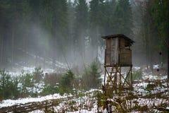 Cabina dei cacciatori in un legno nebbioso fotografie stock