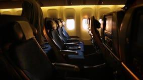 Cabina dell'aeroplano con i passeggeri che imbarcano e che si siedono con una luce di tramonto archivi video