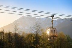Cabina dell'attaccatura funicolare su una corda contro il contesto delle montagne al tramonto Immagini Stock Libere da Diritti