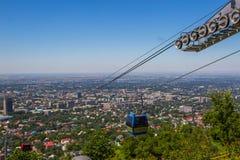 Cabina della cabina di funivia alla vista della città di Almaty, il Kazakistan Fotografie Stock