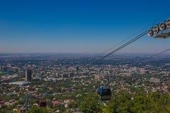Cabina della cabina di funivia alla vista della città di Almaty, il Kazakistan Fotografie Stock Libere da Diritti