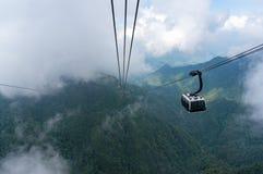 Cabina della cabina di funivia alta nelle montagne con le nuvole Fotografie Stock