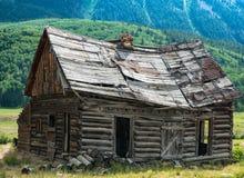 Cabina di ceppo del pioniere di Colorado vicino alla collina crestata fotografie stock libere da diritti