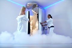 Cabina di congelamento entrante della donna alla clinica di cosmetologia fotografia stock libera da diritti