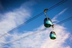 Cabina di funivia aerea del tram che va su, durante il tramonto, con erba verde Fotografie Stock Libere da Diritti