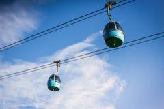 Cabina di funivia aerea del tram che va su, durante il tramonto, con erba verde Immagini Stock
