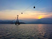 Cabina di funivia con il cielo nuvoloso sui precedenti al tramonto immagine stock
