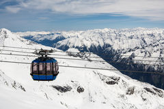 Cabina di funivia con il pendio dello sci in montagne vicino Immagini Stock