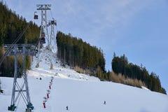 Cabina di funivia della gondola di Funifor sul pendio di montagna nel giorno di inverno soleggiato, stazione sciistica nelle alpi Immagini Stock