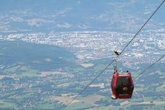 Cabina di funivia di Chamrousse sopra la città di Grenoble Fotografia Stock