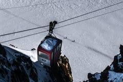 Cabina di funivia di Decommisioned che pende dai cavi sopra il traversi degli sciatori Fotografia Stock