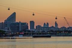 Cabina di funivia di Tamigi sopra i Docklands al tramonto Immagine Stock