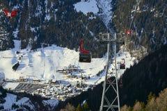 Cabina di funivia discendente andante della gondola di funifor sul pendio di montagna nel giorno di inverno soleggiato, stazione  Fotografie Stock Libere da Diritti