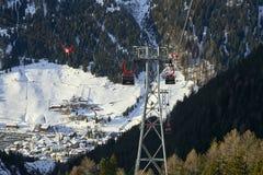 Cabina di funivia discendente andante della gondola di funifor sul pendio di montagna nel giorno di inverno soleggiato, stazione  Fotografia Stock