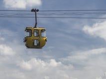 Cabina di funivia gialla d'annata con il fondo del cielo blu Fotografie Stock