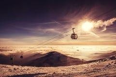 Cabina di funivia in montagna di inverno, paesaggio inverso nell'alba Fotografia Stock Libera da Diritti