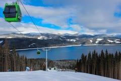 Cabina di funivia, pendio dello sci e lago del mountainl Immagine Stock