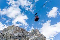 Cabina di funivia rossa che va ad una cima della montagna nelle dolomia Immagini Stock