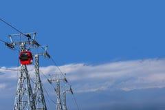 Cabina di funivia rossa su cielo blu con il fondo della nuvola nel Kashmir immagini stock