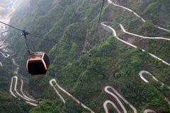 Cabina di funivia sopra il viale dicollegamento in montagna di Tianmen, Cina Fotografia Stock