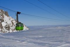 Cabina di funivia sopra la montagna nevosa Fotografia Stock