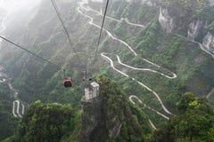Cabina di funivia sopra la strada di bobina in montagna di Tianmen, Cina fotografia stock
