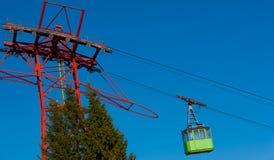 Cabina di funivia verde che accelera verso l'alto Sinistro più basso visto alcuni abeti immagini stock