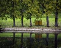 Cabina di legno gialla fra gli alberi sulla riva Fotografie Stock Libere da Diritti