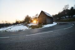 Cabina di legno nel tramonto, inverno con la via scura nella parte anteriore della vista, neve Immagini Stock Libere da Diritti