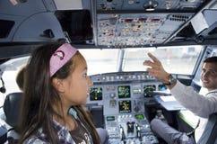 Cabina di pilotaggio dell'aeroplano con il pilota e l'ospite Immagini Stock