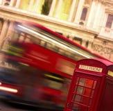 Cabina di telefono con la corsa del bus Immagine Stock