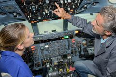 Cabina do piloto de aviões de explicação dos controles do homem à jovem senhora fotografia de stock royalty free
