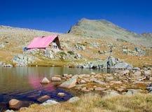 Cabina e un lago glaciale in su in sosta nazionale Pirin, Bulgaria Fotografia Stock