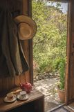Cabina en el bosque con los granjeros chaqueta y sombrero Fotografía de archivo libre de regalías