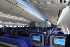 Cabina interna dell'aeroplano con i sedili, i passeggeri ed il bagaglio Fotografia Stock