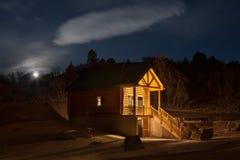 Cabina rústica en el bosque en la noche foto de archivo libre de regalías