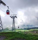 Cabina roja del cable abajo de Mannlichen con la visión escénica en la dirección a Grindelwald, Suiza, Europa Fotografía de archivo