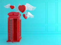 Cabina telefonica rossa di Londra con cuore rosso nella stanza blu Tra di amore fotografia stock