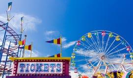 Cabina y paseos de boleto en un carnaval contra el cielo azul Imagenes de archivo