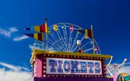 Cabina y paseos de boleto en un carnaval contra el cielo azul Foto de archivo