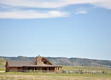Cabina y yarda de registro del verano en las colinas Fotos de archivo libres de regalías