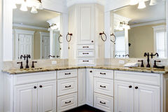 Cabinas de cuarto de baño principales blancas grandes de lujo con los fregaderos dobles.