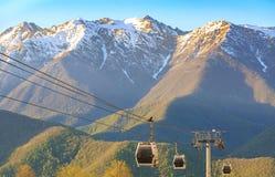 Cabinas de funicular en el fondo de bosques verdes y de montañas coronadas de nieve en la primavera en la puesta del sol Imagenes de archivo